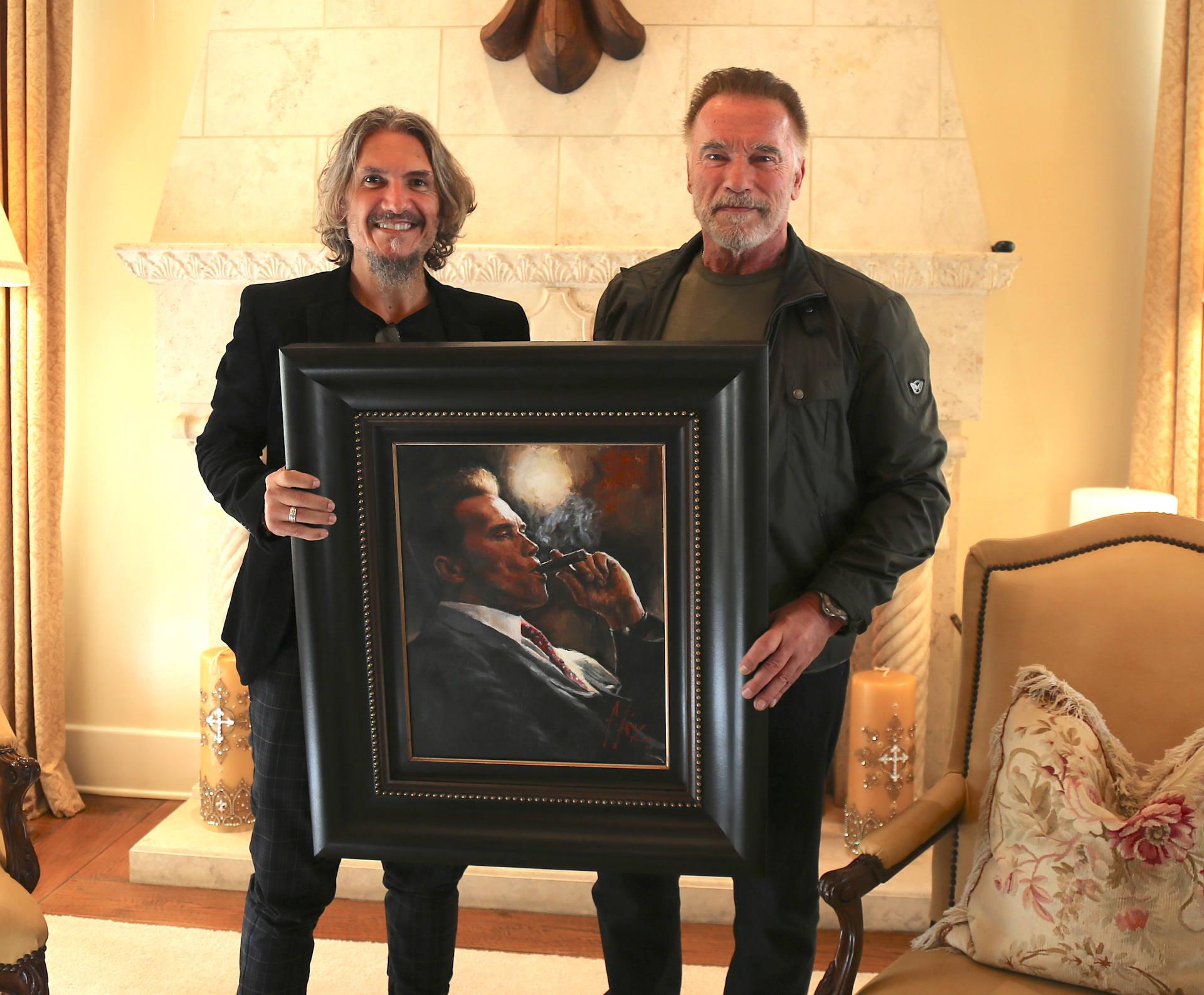 Arnold Schwarznegger holding portrait next to Fabian Perez