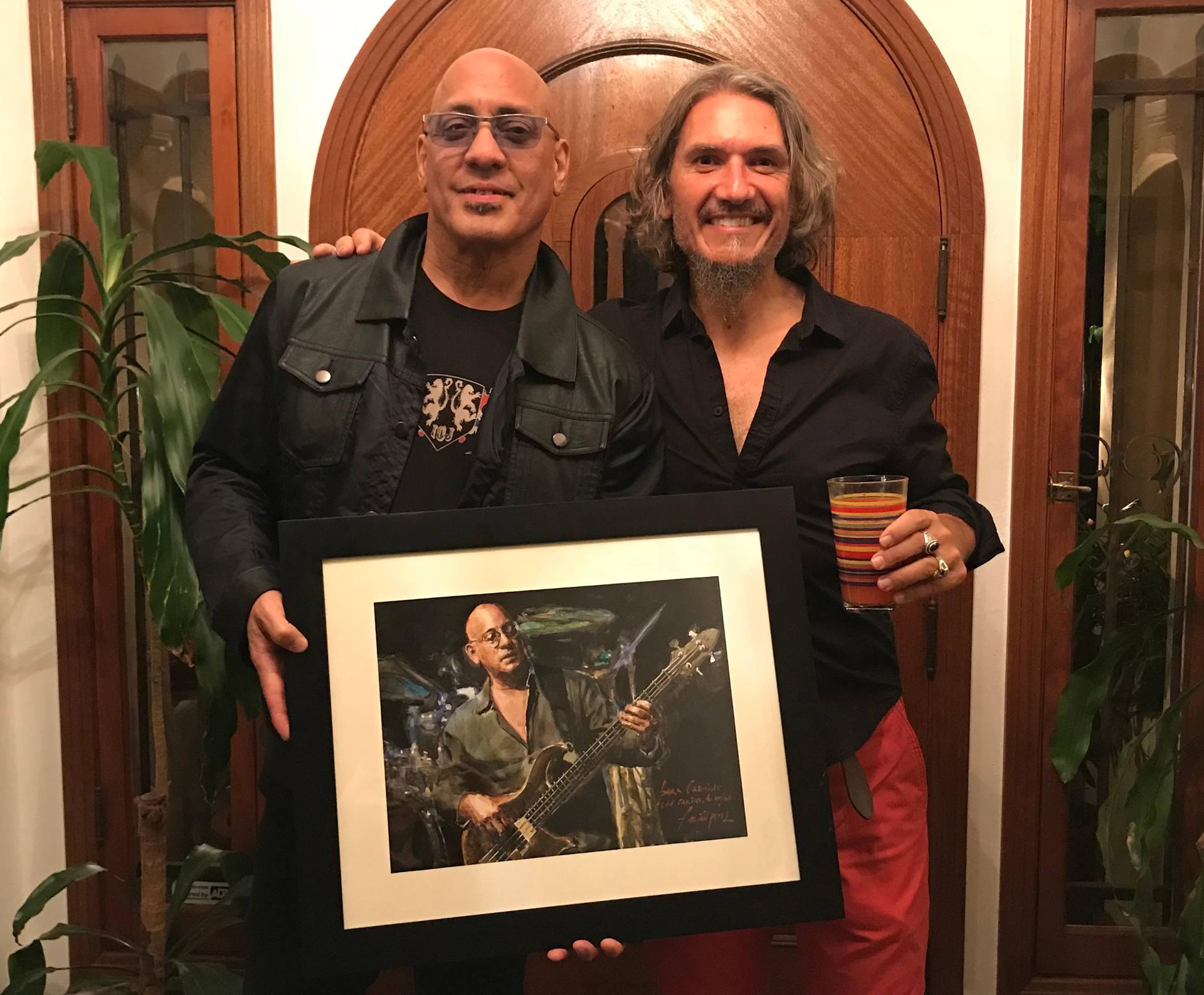 Carmine Rojas holding portrait next to Fabian Perez