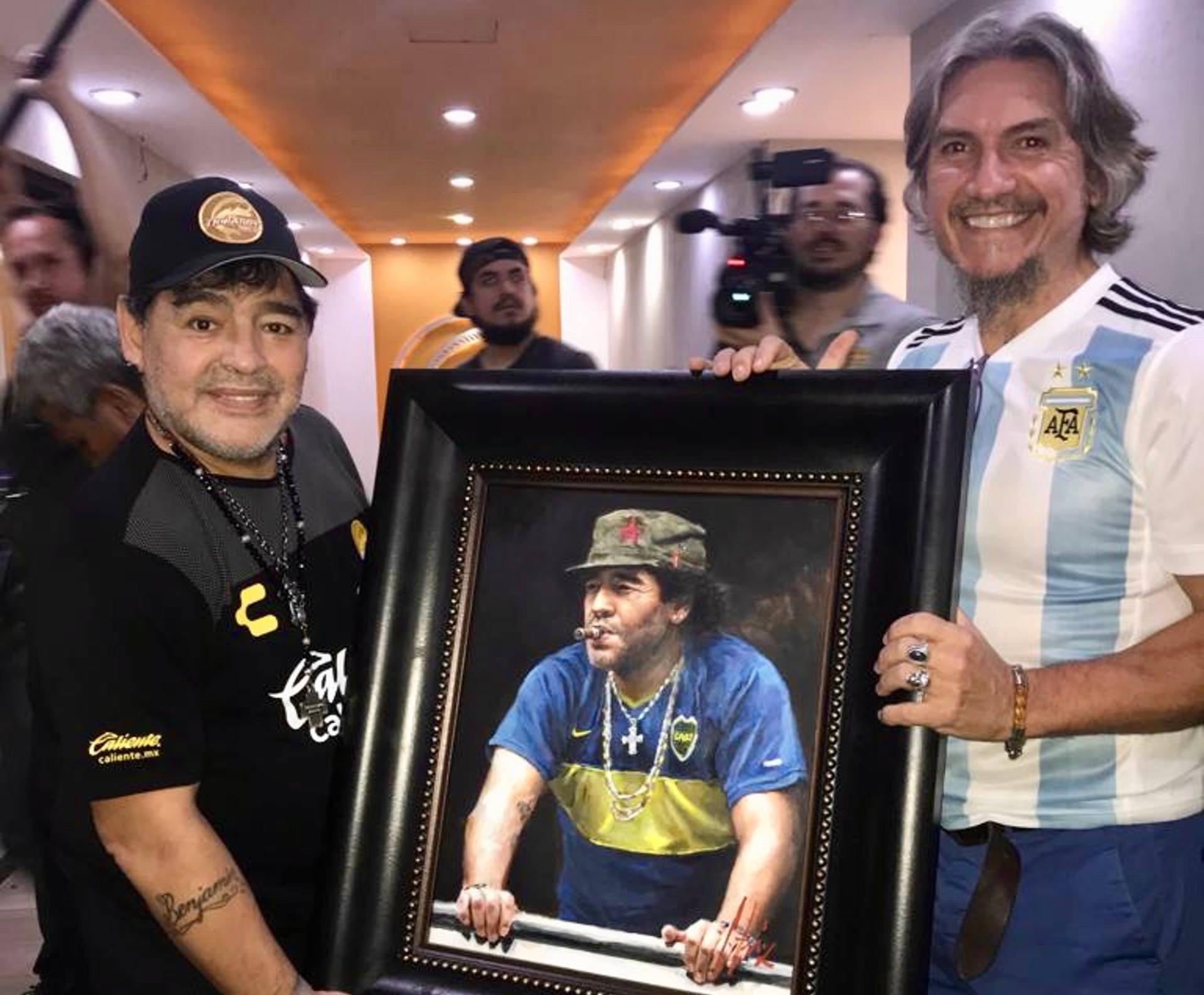 Diego Maradona holding portrait next to Fabian Perez