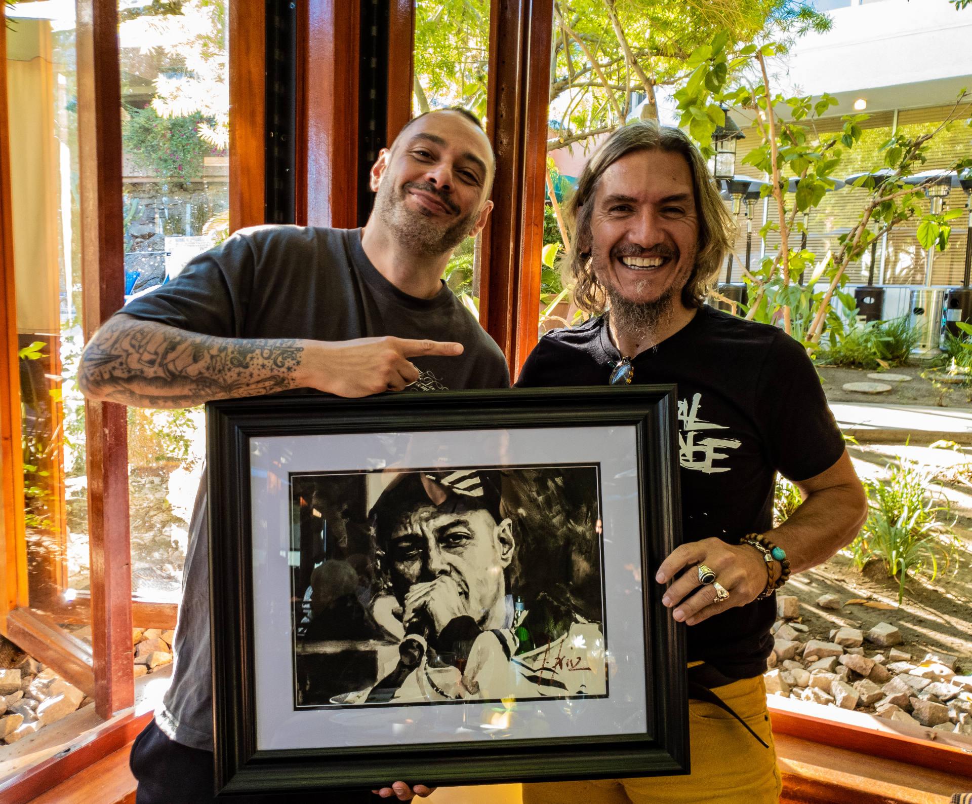 Fabri Fibra standing next to Fabian Perez holding portrait