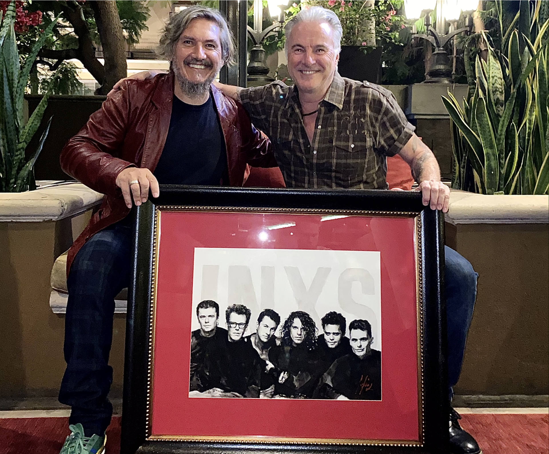 Garry Gary Beers holding portrait next to painter Fabian Perez