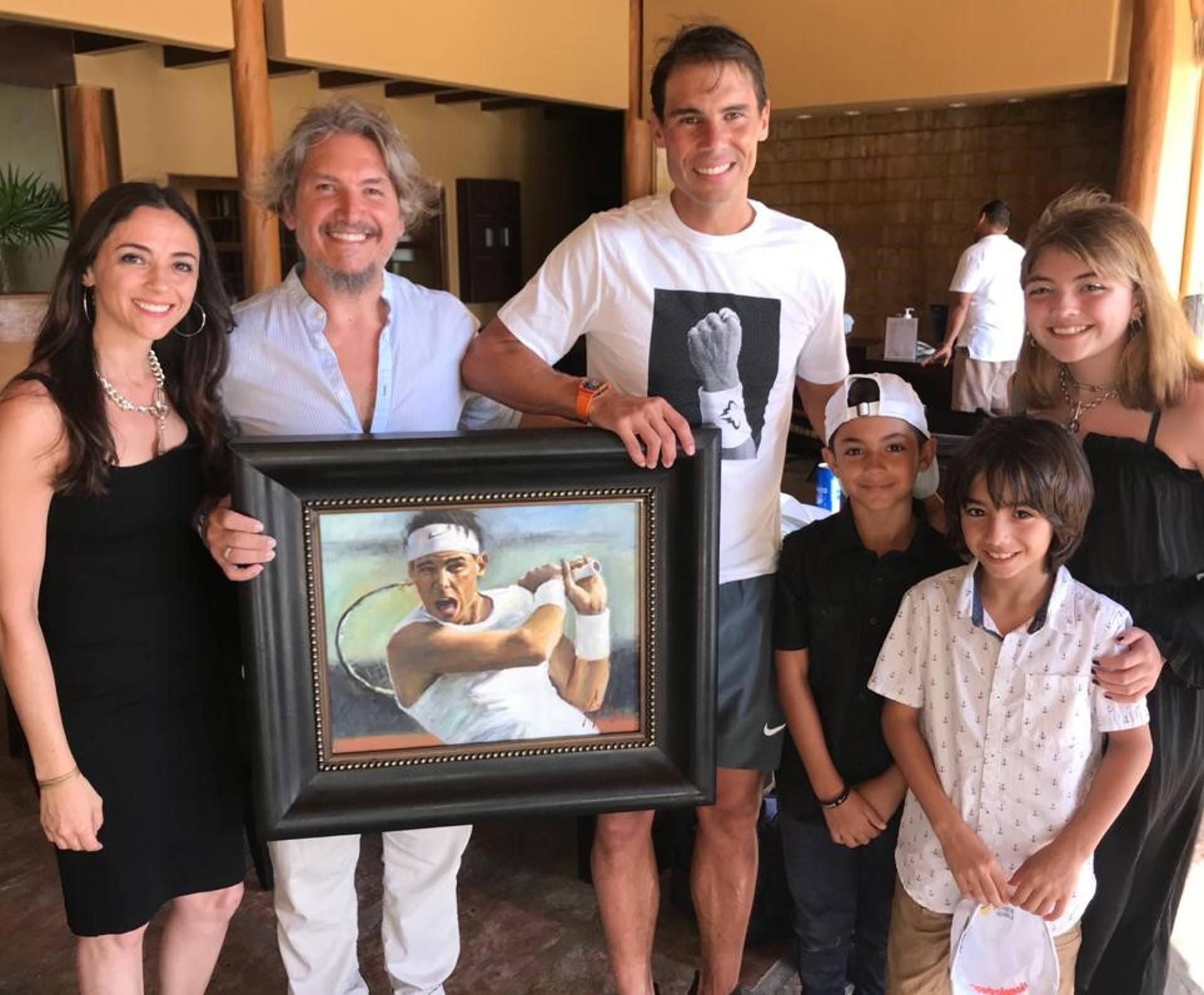 Rafael Nadal holding portrait next to Fabian Perez and family