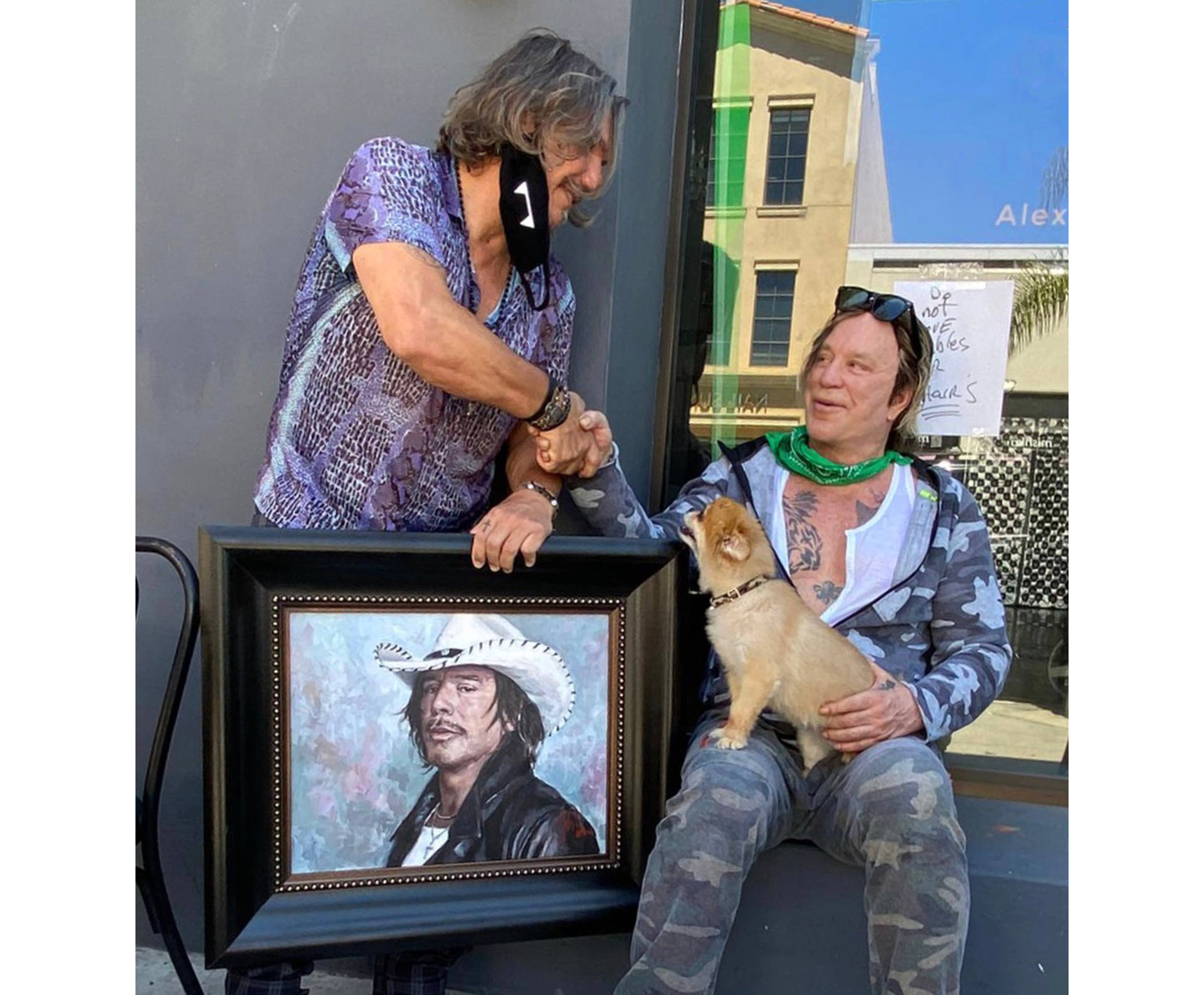 Mickey Rourke sitting next to portrait alongside painter Fabian Perez