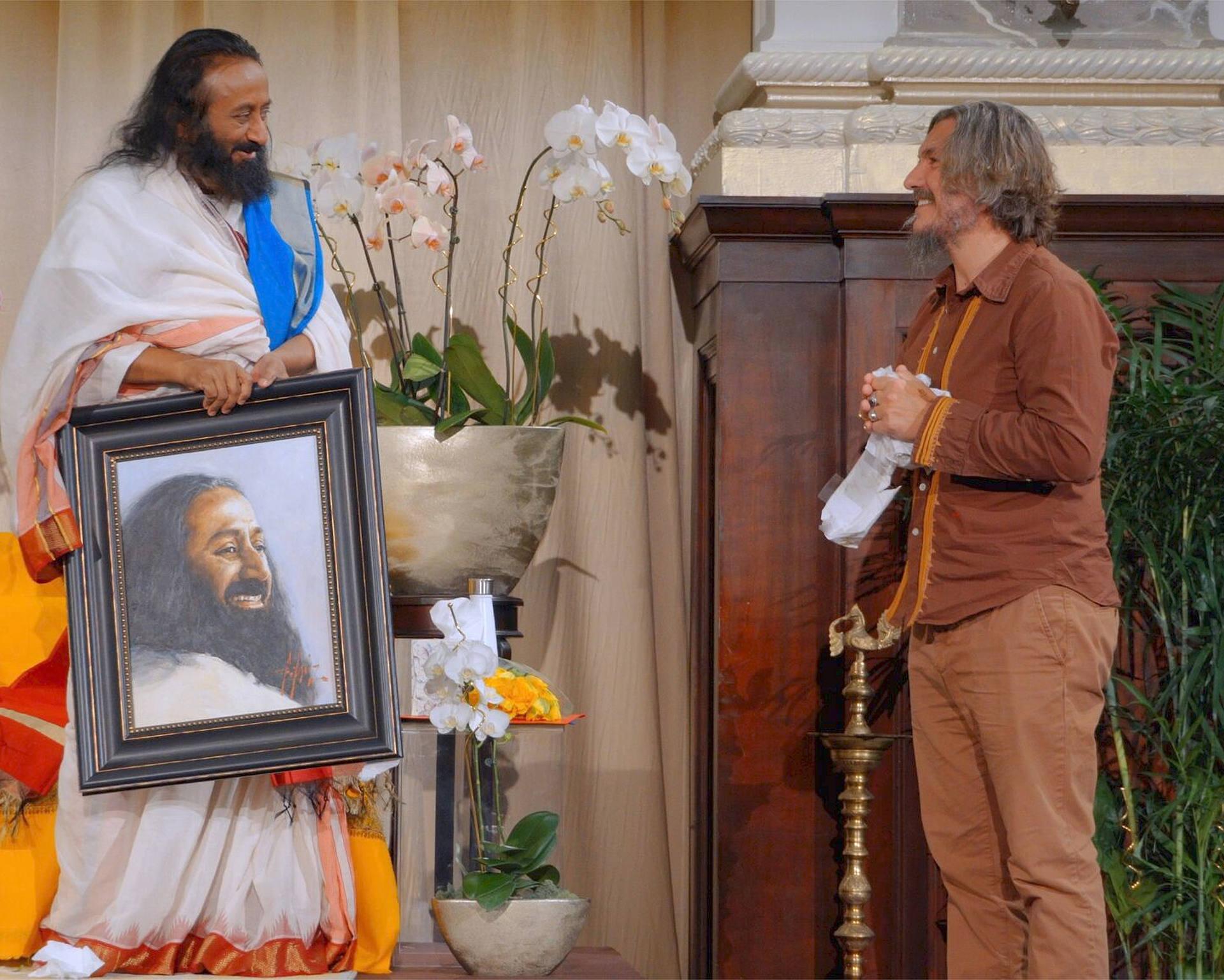 Sri Sri Shankar standing next to portrait by Fabian Perez