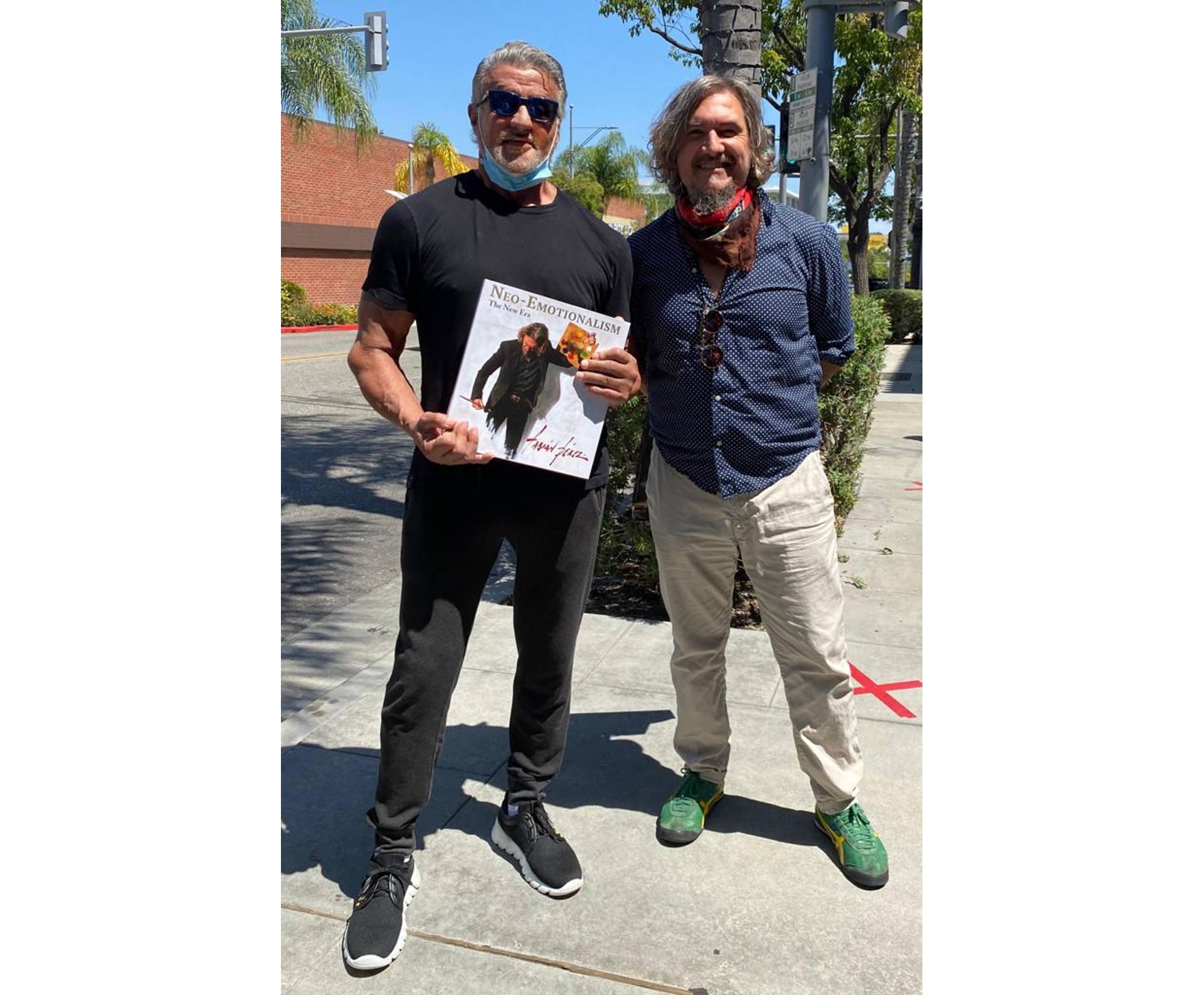 Sylvester Stallone holding art book next to Fabian Perez