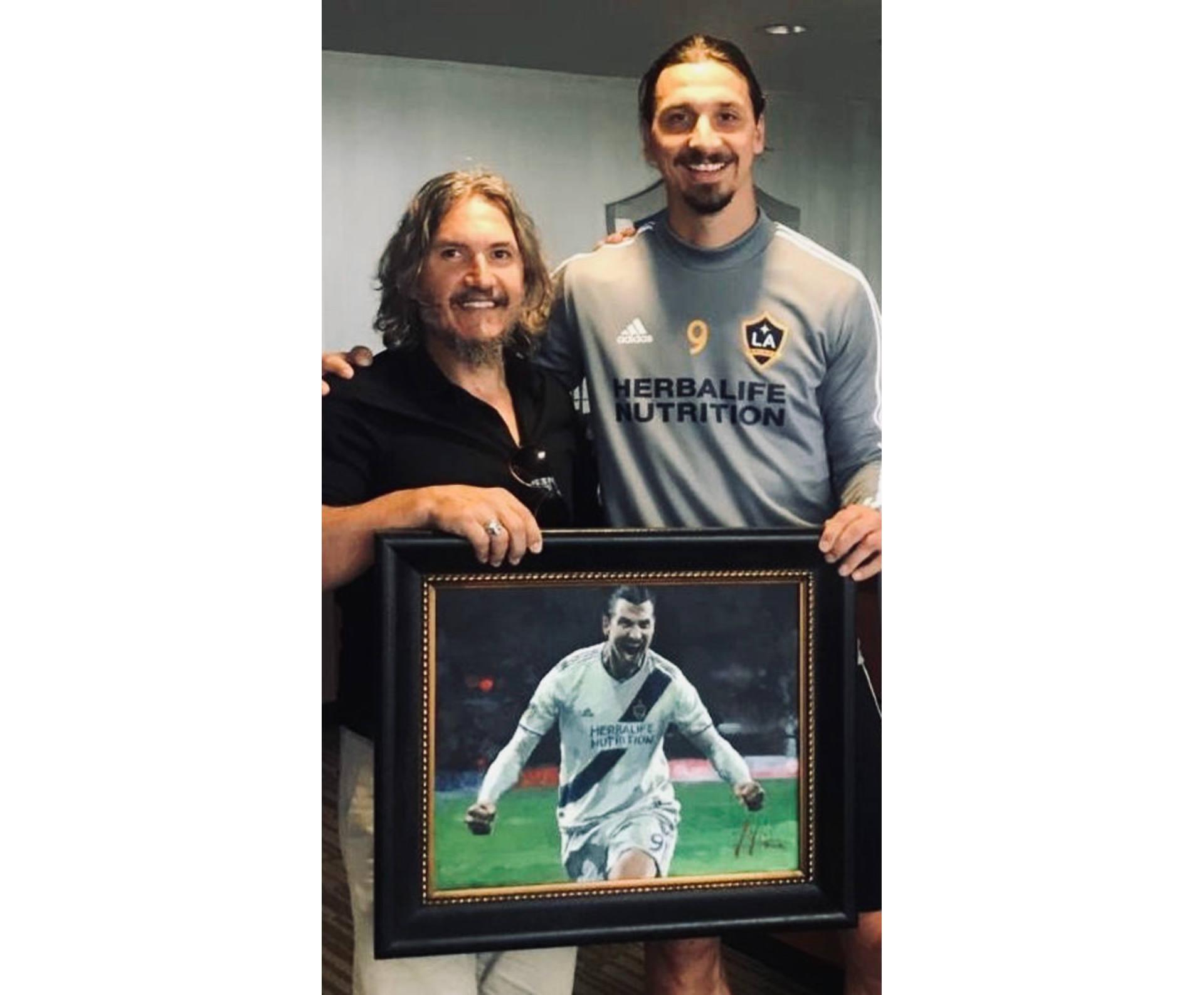 Zlatn Ibrahimović holding portrait next to painter Fabian Perez